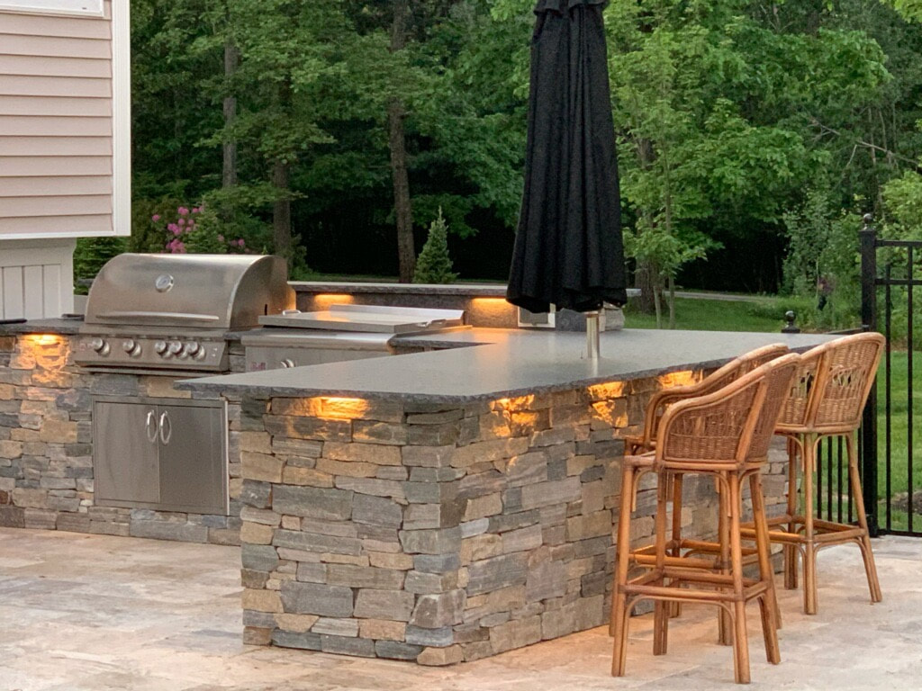 Custom outdoor kitchen, patio, stone walls, landscape lighting, steps and paths.